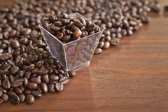 Roasted coffee beans in an old plastic box and heap of coffee pu. T on wooden table. Top view and copy space Stock Photography