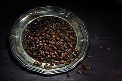 Roasted coffee beans on an old silver plate on a dark brown woo Stock Photo