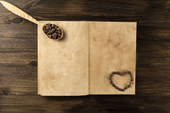 Roasted coffee beans on old vintage open book. Menu, recipe, mock up. Royalty Free Stock Photography