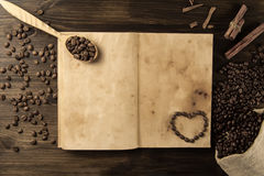 Roasted coffee beans on old vintage open book. Royalty Free Stock Images