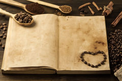 Roasted coffee beans on old vintage open book. Royalty Free Stock Photo