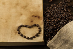 Roasted coffee beans on old vintage open book. Menu, recipe, mock up. Stock Image