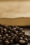 Roasted coffee beans on old vintage open book. Stock Images