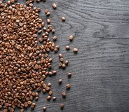 Roasted coffee beans on the old wooden background. Top view. Stock Photography