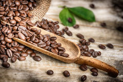 Roasted coffee beans with old wooden scoop Royalty Free Stock Photos
