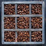 Roasted coffee beans in old wooden tray. Stock Images