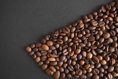 Roasted coffee beans over black paper background Stock Image