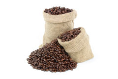 Roasted coffee beans over white. Still picture displaying roasted coffee beans spilled on pile and in burlap sacks over white background Stock Photos