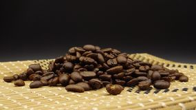Roasted coffee beans over wood on black background stock images