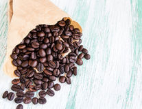 Roasted coffee beans in paper bags on wooden background Royalty Free Stock Photography