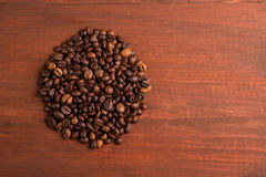 Roasted coffee beans pile from top on the table. Roasted coffee beans pile from top on the wooden table Royalty Free Stock Photo