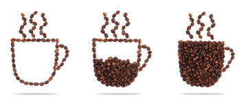 Roasted coffee beans placed in the shape of a cup and saucer on. A white surface Royalty Free Stock Image