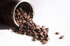 Roasted coffee beans poured from a bottle Stock Photography