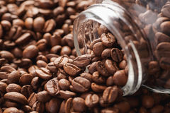 Roasted coffee beans poured from glass jar Royalty Free Stock Photo