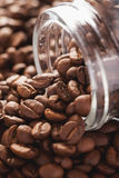 Roasted coffee beans poured from glass jar Stock Photo