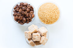 Roasted coffee beans, raw sugar cubes, and brown sugar in the glass bowls isolated Royalty Free Stock Photos