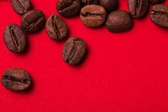 Roasted coffee beans on red background. Color surge trend. Macro royalty free stock image