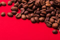 Roasted coffee beans on red background. Color surge trend. Macro stock image