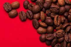 Roasted coffee beans on red background. Color surge trend. Macro royalty free stock photography