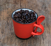 Roasted  coffee  beans  in red cup on the old background Royalty Free Stock Photography