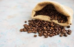 Roasted coffee beans. In burlap bag on old table Royalty Free Stock Photos