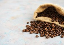 Roasted coffee beans. In burlap bag on old table Stock Image