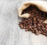 Roasted coffee beans. In burlap bag on old table Royalty Free Stock Photography