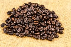 Roasted coffee beans on sack cloth Royalty Free Stock Images
