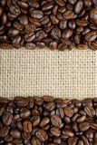 Roasted coffee beans on sackcloth. Background Stock Photos