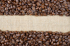 Roasted coffee beans on sackcloth. Background Royalty Free Stock Photo