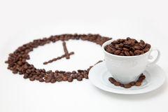 Roasted coffee beans in shape of clock and white cup Stock Photography