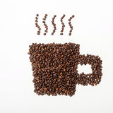 Roasted coffee beans in the shape of a cup. On a white surface Royalty Free Stock Images