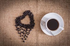 Roasted coffee beans in the shape of a heart and coffee cup Stock Image