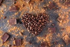 Roasted coffee beans in the shape of a heart on the dark stone background with dissipate cocoa, pieces of chocolate and beans. Sel Royalty Free Stock Images