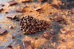 Roasted coffee beans in the shape of a heart on the dark stone background with dissipate cocoa, pieces of chocolate and beans. Sel Royalty Free Stock Photography
