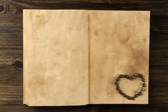 Roasted coffee beans in shape of heart on old vintage open book. Menu, recipe, mock up. Royalty Free Stock Photography