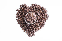 Roasted coffee beans on shot glass and surrounding as a heart shape Stock Image