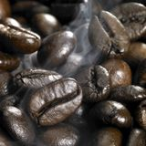 Roasted coffee beans and smoke Royalty Free Stock Photos