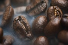 Roasted coffee beans with smoke. Coffee Background royalty free stock photography