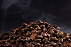 Roasted coffee beans with smoke. On a dark background Royalty Free Stock Photography