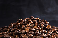 Roasted coffee beans with smoke. On a dark background Stock Photo