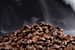 Roasted coffee beans with smoke. On a dark background Stock Photography