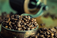 Roasted coffee beans spilled freely on a wooden table. Coffee beans in a dish for ground coffee. Stock Images