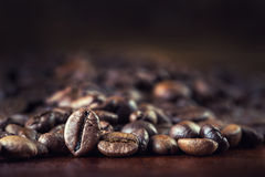 Roasted coffee beans spilled freely on a wooden table. royalty free stock image