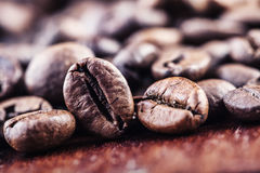 Roasted coffee beans spilled freely on a wooden table. Royalty Free Stock Photography