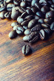 Roasted coffee beans spilled freely on a wooden table. Royalty Free Stock Photo