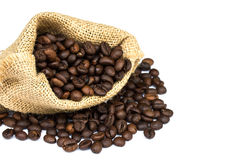Roasted coffee beans spilled on pile and in burlap sacks Royalty Free Stock Photography
