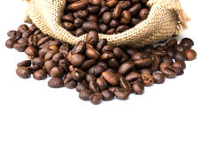 Roasted coffee beans spilled on pile and in burlap sacks Stock Image