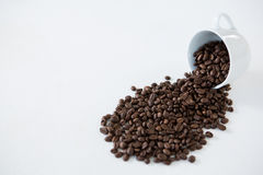 Roasted coffee beans spilling out of cup. On wooden table Royalty Free Stock Photos