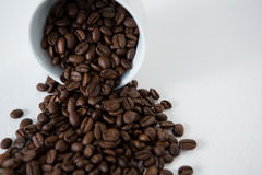 Roasted coffee beans spilling out of cup. On wooden table Royalty Free Stock Image